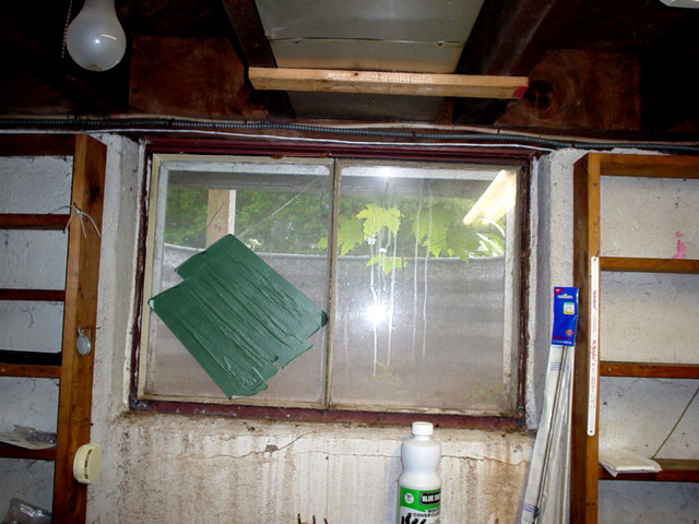 An Old Rotting Basement Window Set In A Rusty Steel Frame With Patch Over