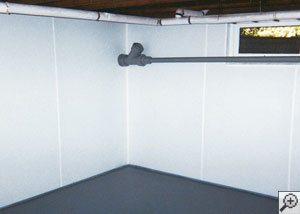 A basement wall that's been upgraded with a plastic paneling that will keep it waterproof and attractive.