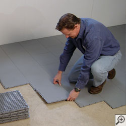 A waterproofing contractor installing waterproof basement sub floor tiles in a basement.
