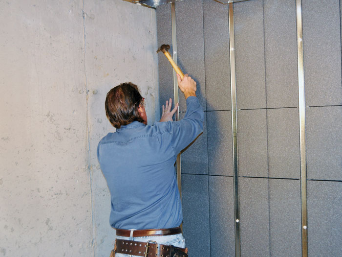 An Installer Mounting Prefinished, Insulated Basement Wall Panels.