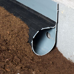 A custom-designed crawlspace drainage pipe, sloping water towards the sump pump.