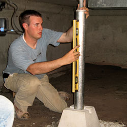 A crawl space contractor installing a support jack to add structural stability to the home