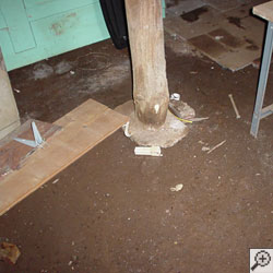A dirt basement floor and wood support beam.