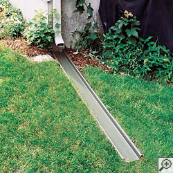 A gutter downspout extension installed in a lawn.