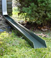 A gutter downspout extension installed in a lawn area.