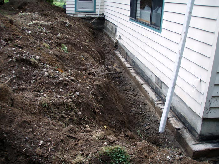 Landscaping Around Home Foundation : House with the exterior soils excavated to expose foundation