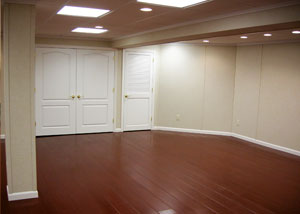 A finished basement with faux wood flooring and insulated basement wall panels