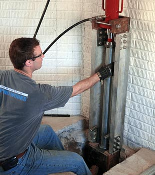 a contractor installing a foundation push pier system