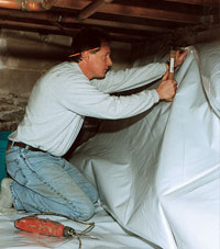 A contractor installing a crawl space vapor barrier in a home