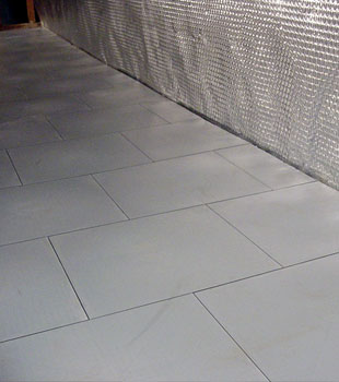 Basement sub floor tiles installed on a concrete slab floor.