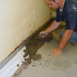 Restoring the concrete floor after a basement drain system is installed.