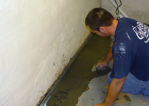 Restoring a concrete slab floor with fresh concrete after jackhammering it and installing a weeping tile system.