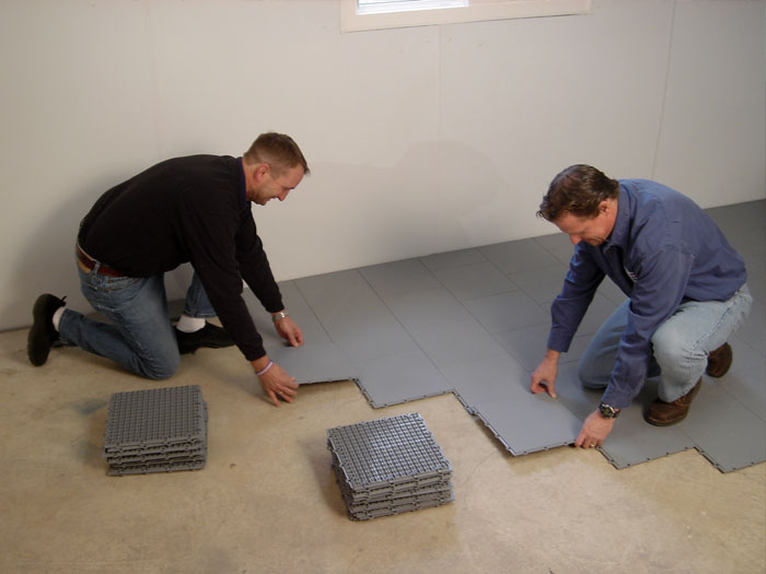 Two Contractors Installing ThermalDry® Floor Matting Tiles On A Basement  Floor.