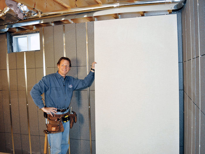 A Basement Contractor Holding A Wall Board And Standing In Front Of An  Insulated Basement Wall