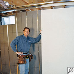 A basement contractor holding a wallboard and standing in front of an insulated basement wall.
