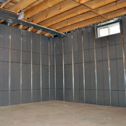 Basement walls that have studs and insulation installed on them.