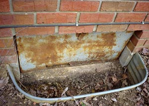 An old, rusty crawl space access well and door.