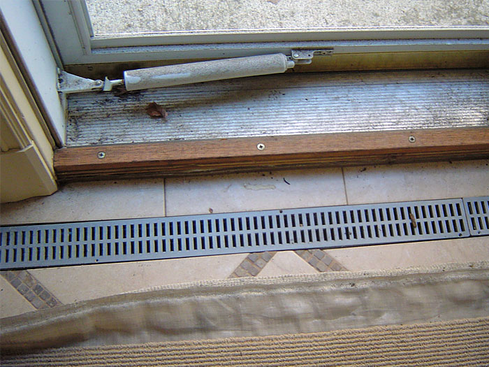 basement entryway with our grated basement drainage system spanning