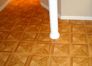 Parquet flooring tiles installed in a corner and around a support post in a basement.