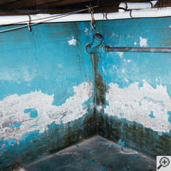 A basement with bright blue waterproof paint that is heavily peeling and flaking off the walls.