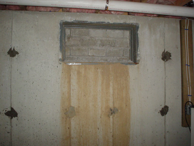 A Basement Window Plugged With Concrete And Leaking Through At The Bottom.