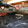 A crawl space with a liner installed on the floor that is showing signs of moisture and flooding.