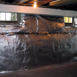 A basement wall vapor barrier and radiant heat barrier system installed in a home.