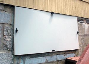 An installed crawlspace door system on a home
