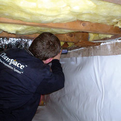A contractor installing a durable crawl space liner on the foundation walls.