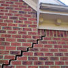 A cracked foundation wall showing a stair-step crack patten in the brick