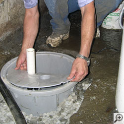 A Contractor Installing A Sump Pump System In The Dirt Floor Of A Basement.