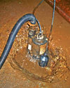 a sump pump system installed in a tiny sump pit in the mud.