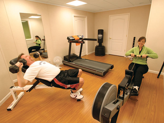 A basement finished with wood laminate flooring to create a personal gym. : basement floors options  - Aeropaca.Org