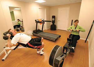 A basement finished with wood laminate flooring to create a personal gym.
