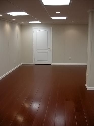 basement floor finished with a simulated wood floor surface